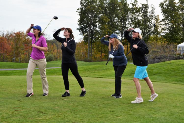 Amy Smith and 3 others posing on the green with their hands up shading their eyes as they look off in the distance for their balls