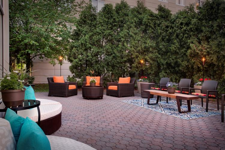 Dusk shot of orange and teal seating at Hilton Garden Inn Saratoga Springs patio