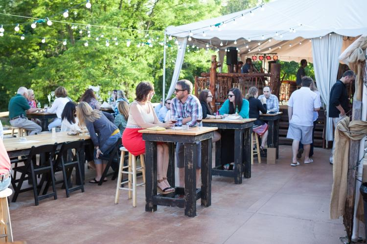 People enjoying the outdoor patio at Saratoga Winery with string lights and some shade