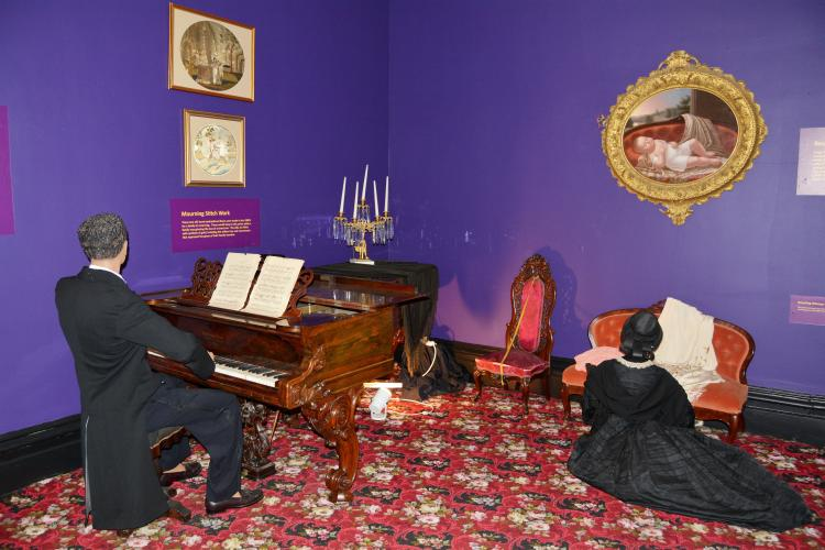 Mourning Room with man playing piano and woman kneeling by couch under portrait of Walworth baby