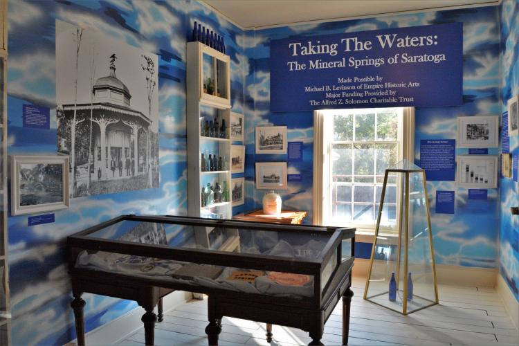 Taking the Waters exhibit, overview of the room with blue multi-colored walls and a glass covered display table