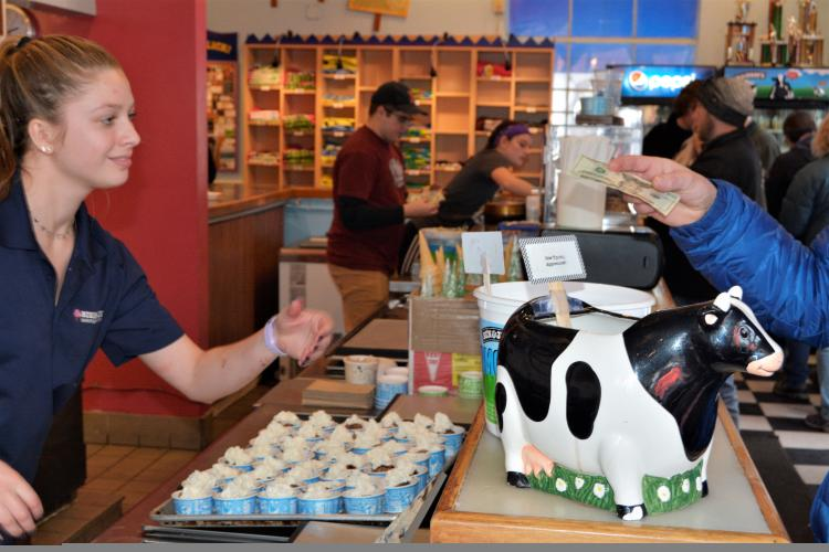 Cashier at Ben and Jerrys taking money at counter