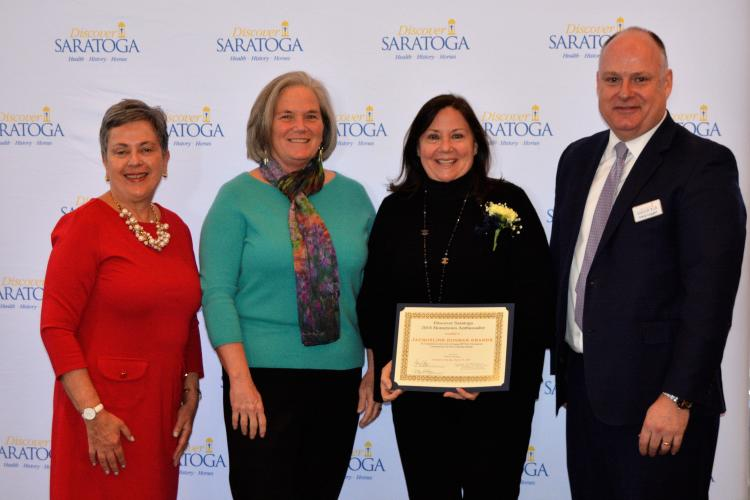 Group of four people standing in front of Discover Saratoga's step and repeat while accepting hometown ambassador award at Saratoga Springs City Center