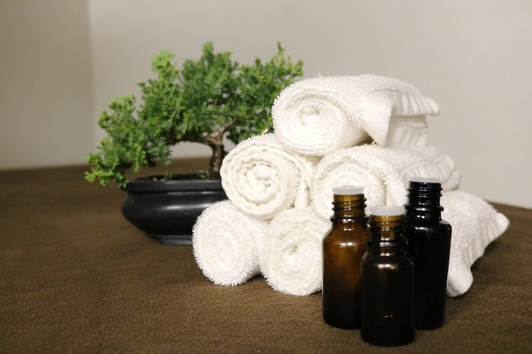 Swedish Hill Farm and Spa pile of rolled towels and 3 bottles of oils displayed