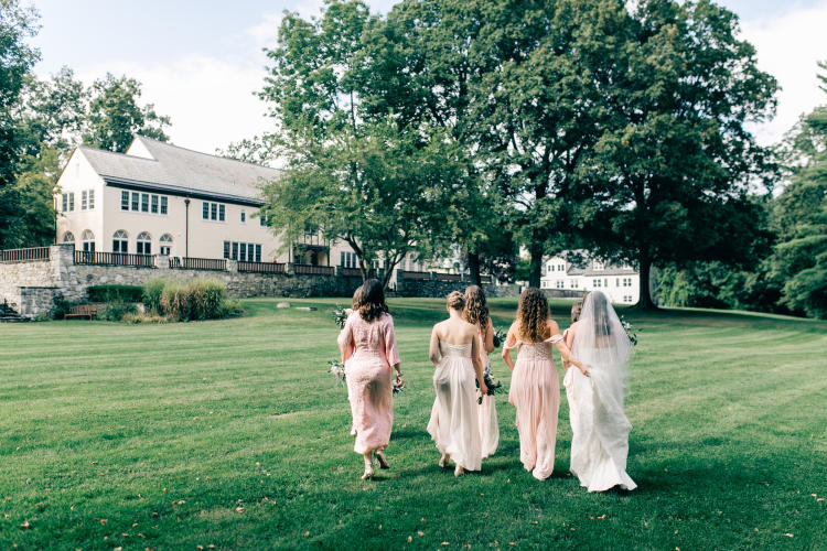 Bride and bridesmaids walking up the back lawns toward the Inn