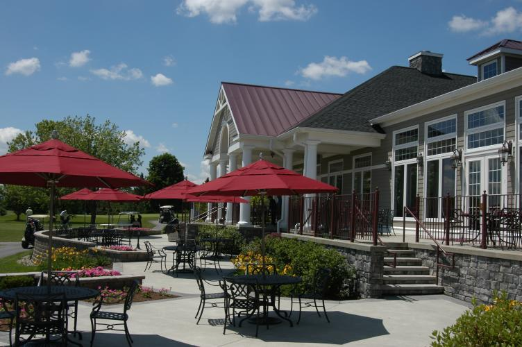 Outdoor seating with red umbrellas at Van Patten Golf Club