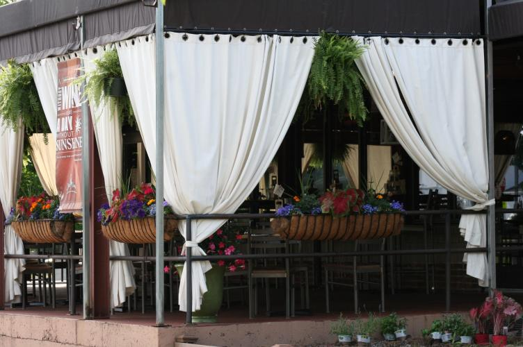 Shot of Pasta Pane Rustic Italian Bistro's patio with white drapes and colorful plants