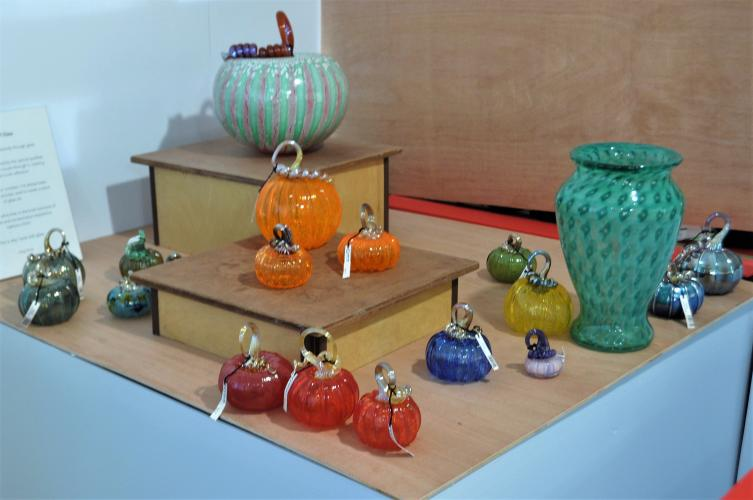 Glass works gallergy Greg Tomb with examples of a vase, bowl and several pumpkins in many colors