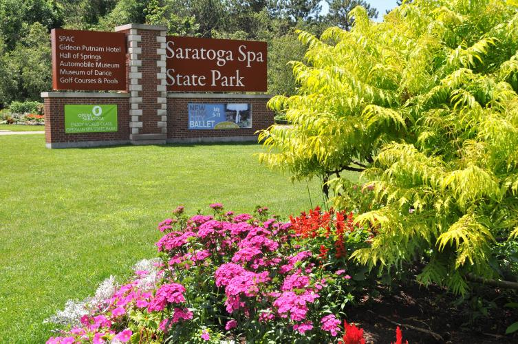 Saratiga Spa State Park sign at entrance with colorful bush and flowers in the foreground
