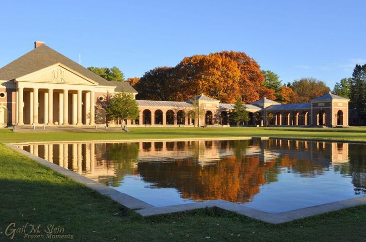 State Park bldg with golden foliage behind it, all shining in the reflecting pool