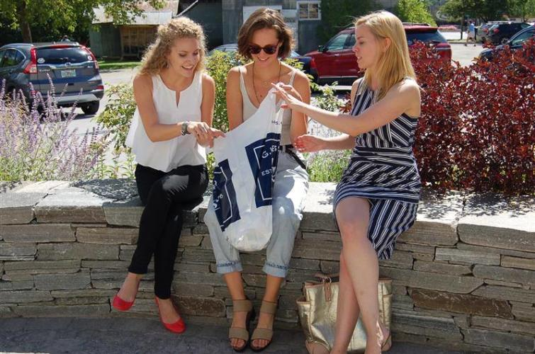 Three women sitting on a stone wall looking into a shopping bag