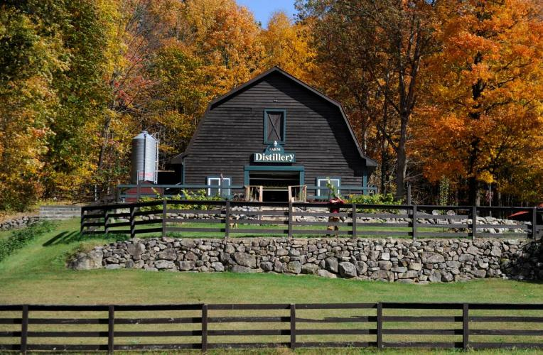 Outdoor shot of brown barn at Springbrook Hollow Farm with two rows of brown fencing and a stone wall in front and autumn foliage behind it.