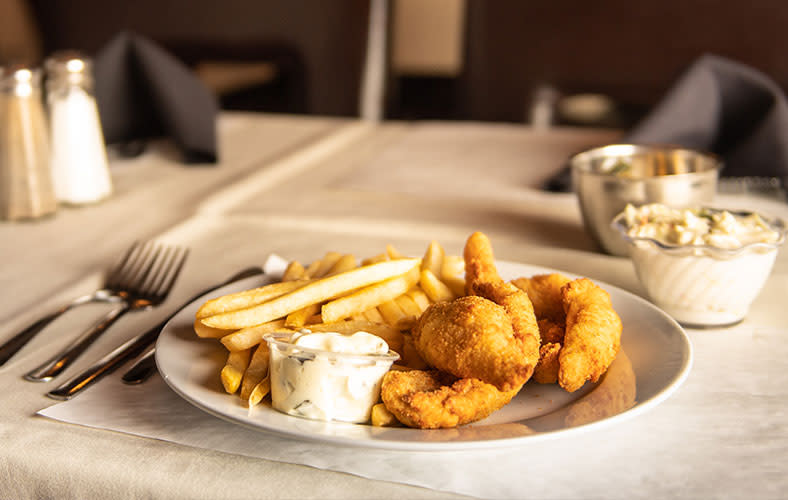 A plate of fried fish with tartar sauce and french fries