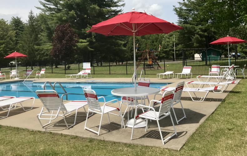 Saratoga RV Park pool and patio area with table amd red umbrellas around the pool