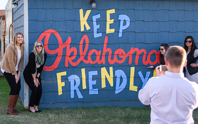 """Group taking photo in front of Bleu Garten's """"Keep Oklahoma Friendly"""" mural"""
