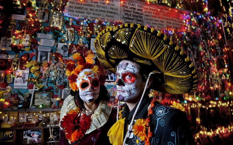 two traditionally face painted people Day of the Dead