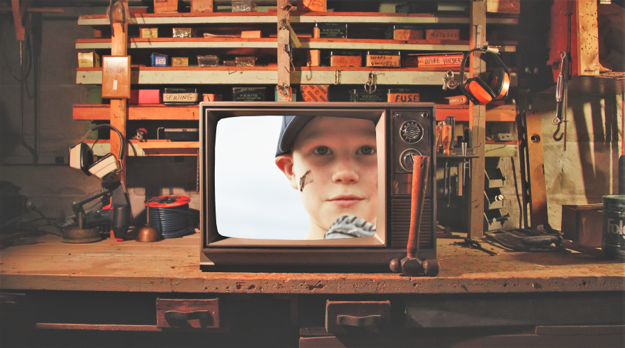 Television sitting on a cluttered work bench with the face of a young boy on the screen