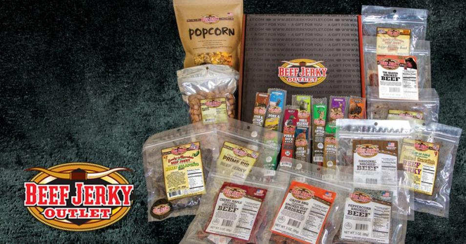 Display of bags of jerky, popcorn and other snacks on gray carpet with logo in lower left hand corner.