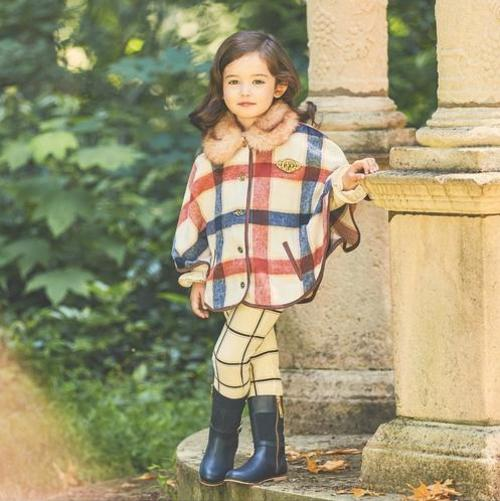 a young child posing in cute plaid fall clothes