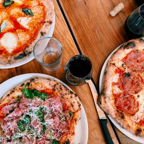 Three pizzas on a wooden table from Nomad Pizza