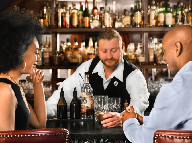 A bartender at Dockum serves a drink to a man with his date