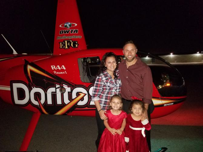A family poses in front of a red DWTA Helicopter before taking a tour