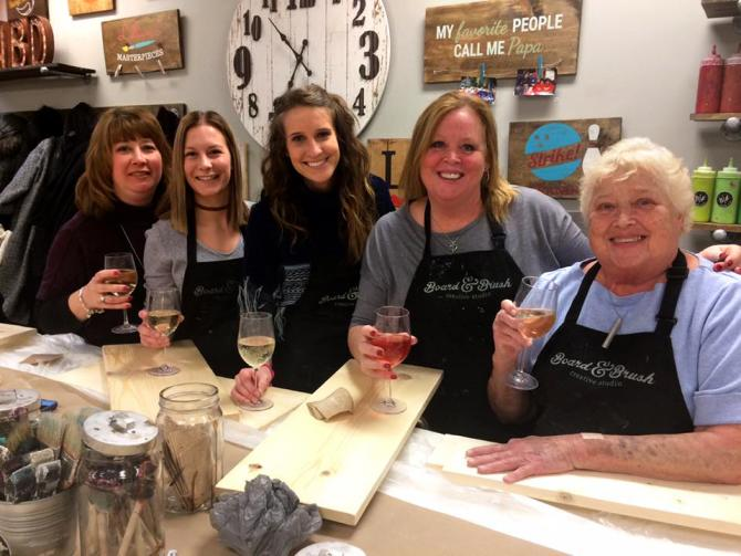 Five women smile for the camera with their wine in hand and boards in front of them ready to be painted