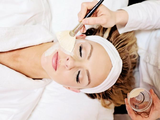 A woman relaxes at a spa while getting a facial