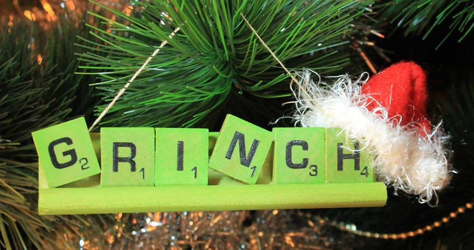 "Christmas tree ornament made out of Scrabble pieces that spells out ""GRINCH"" with a Santa hat on the right corner."
