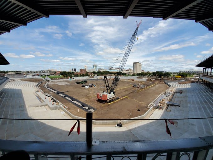 large crane overtop dirt field that will one day be baseball diamond, concrete structures under construction, blue sky overhead overlooking the Wichita skyline in background