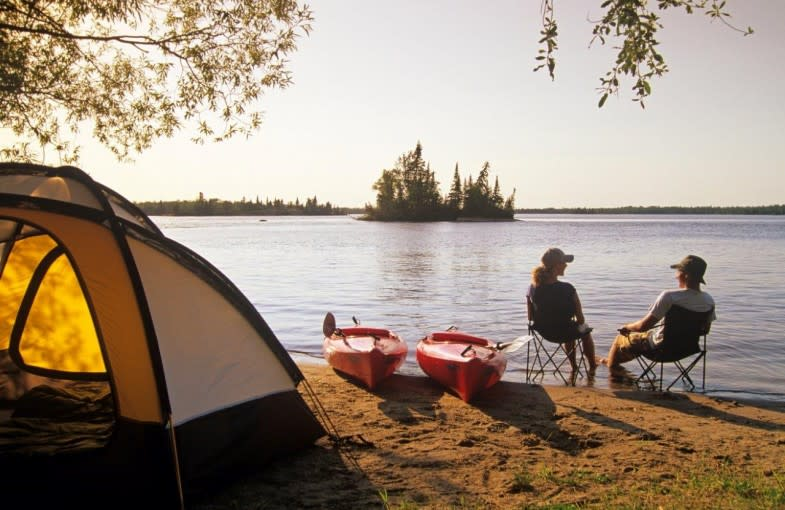 ywo people sitting on a beach in front of their tent and kayaks