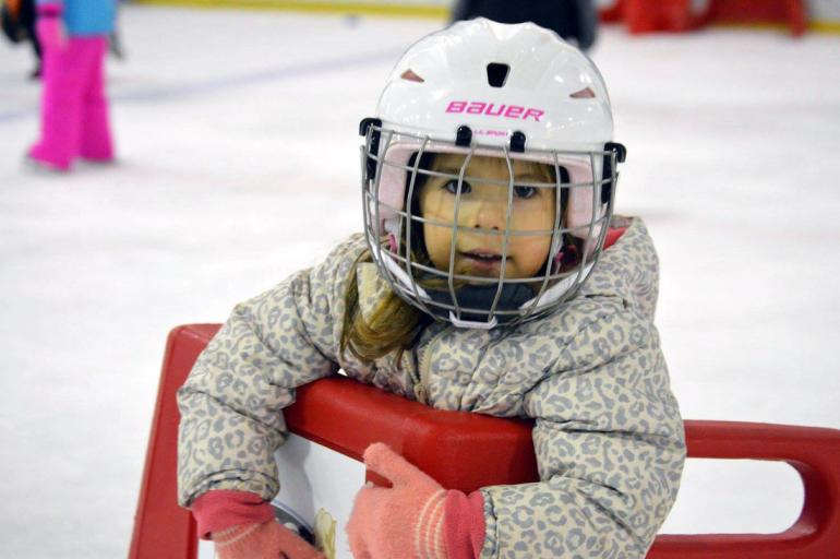 Young child learning to skate at Bill Gray's Regional Iceplex