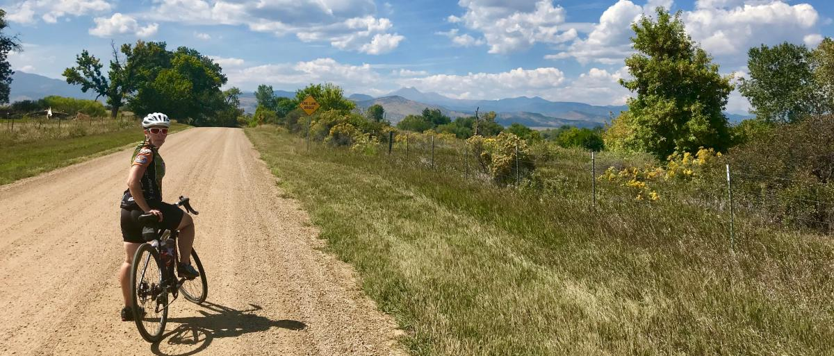 Woman stopped on her bike on a gravel road in Boulder