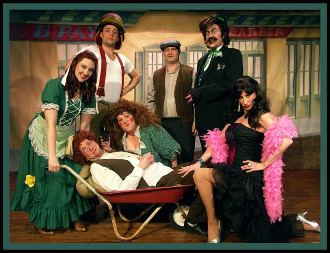 Seven cast members at Mosley Street Melodrama pose on stage in costume