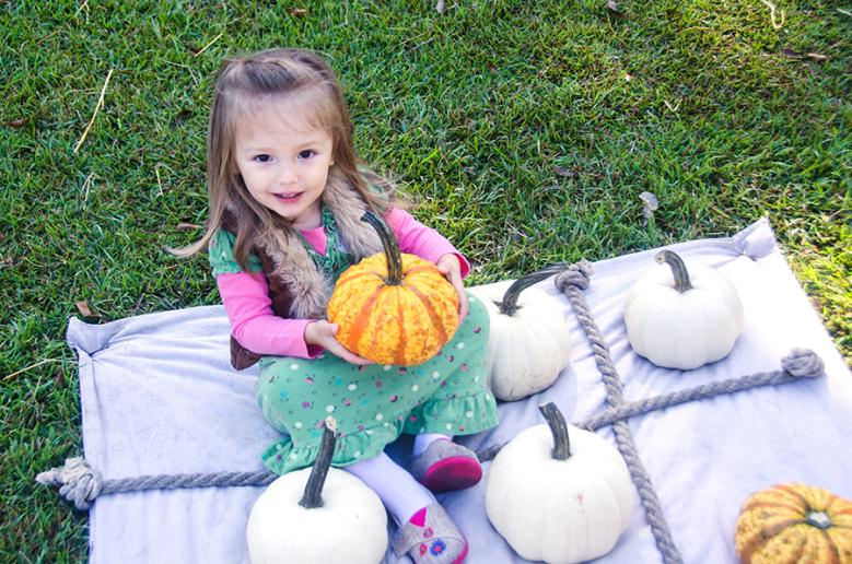Little Girl Holding a Pumpkin