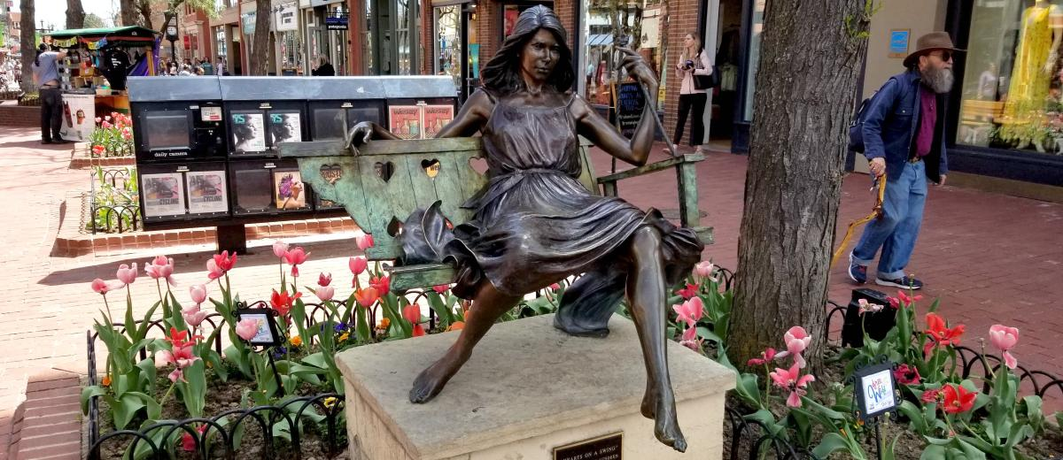 Pearl Street sculpture of a woman on a swing