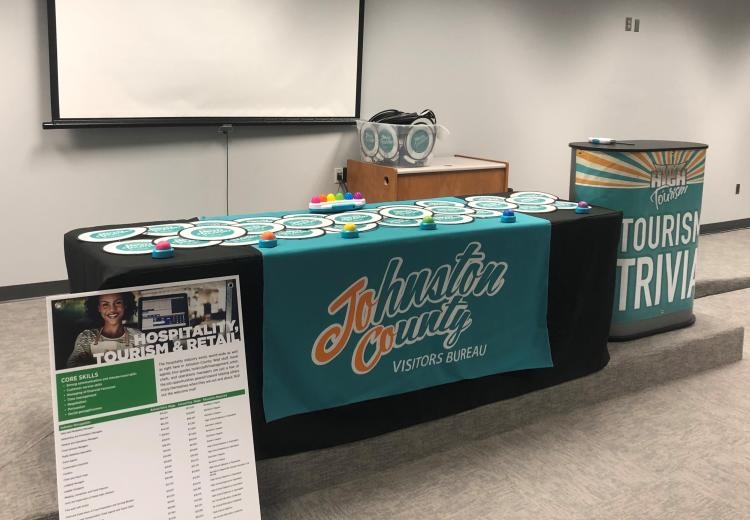 A table set with tourism industry information and gifts sits on a raised platform in a classroom.