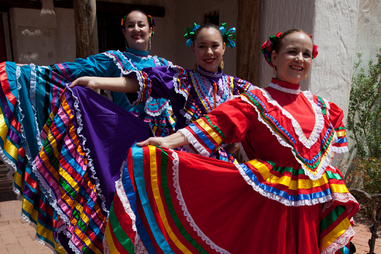 Three dancers hold up their skirts for Ballet Folklorio in Albuquerque, NM