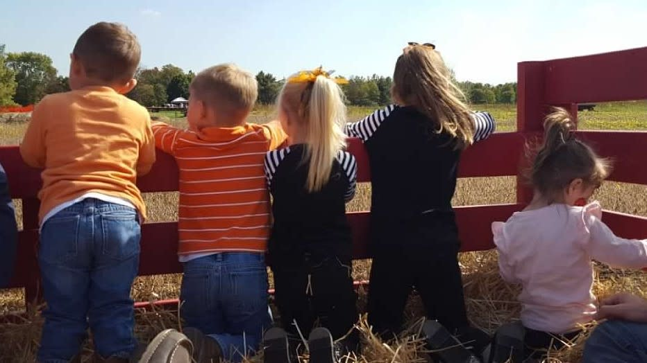 Four children looking out at a field of hay