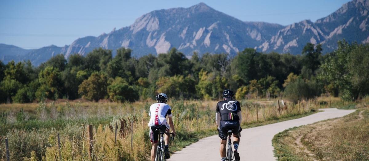 Cyclists on path with Flatirons
