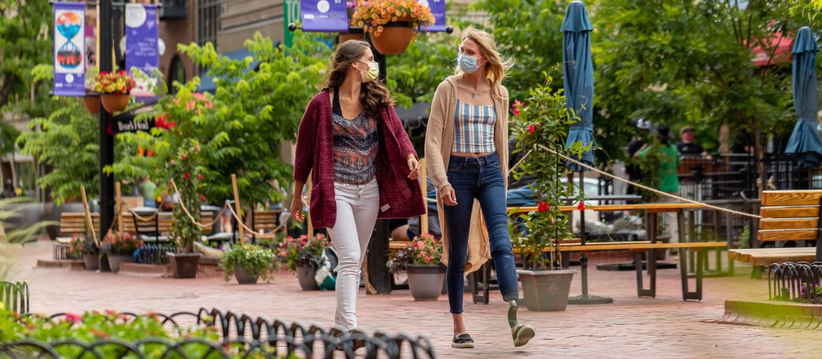 Two women wearing masks walking on Pearl Street