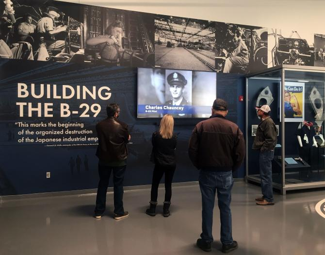 A group of people in the Mezzanine Museum at Doc's hangar watch a video about the B-29's history