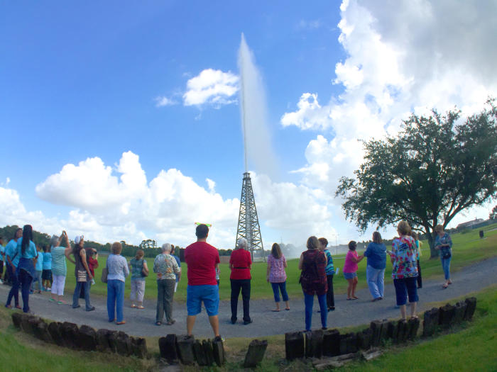 Spindletop Gusher with crowd watching on a pretty day.