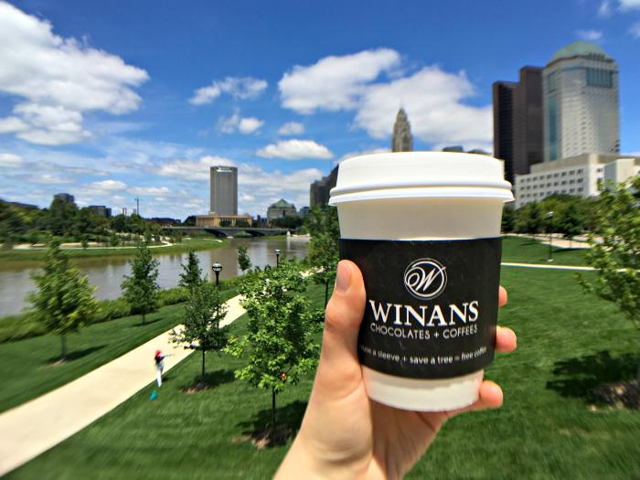Hand holing to-go mug of coffee with Winan's label in front of Scioto Mile park
