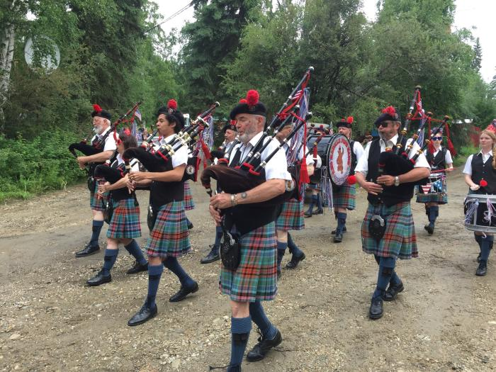 Bag pipers dressed in Scottish kilts playing in formation