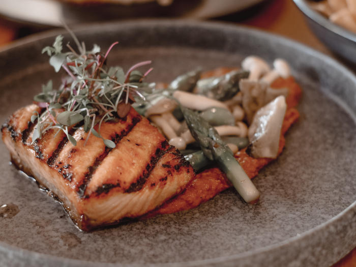 EATS Kitchen at the Hotel Irvine offers a King Salmon entree. The ingredients include snap peas, artichoke, asparagus tips, shimeji mushroom, and Romesco (a new preparation)
