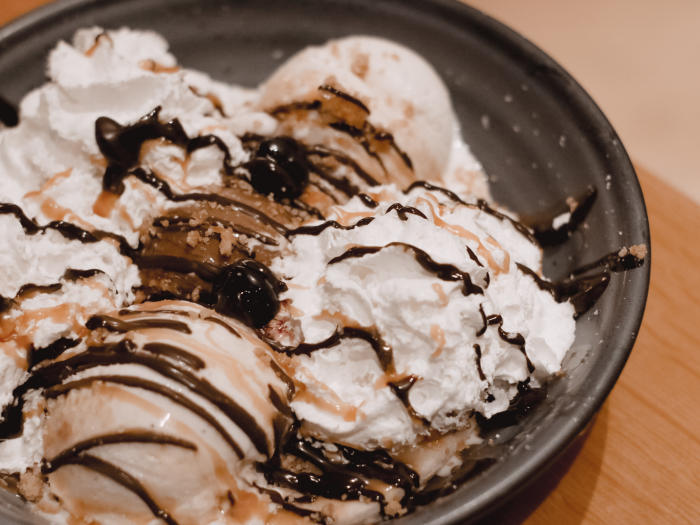 EATS Kitchen at the Hotel Irvine offers a Banana Split dessert. The ingredients include French vanilla & chocolate ice cream, chocolate & caramel sauce, whipped cream, luxardo cherries, and graham cracker crumble.