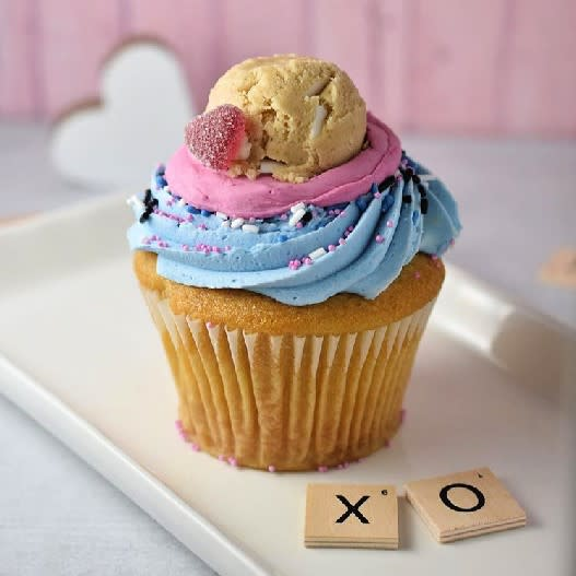 "A cupcake on a plate next to an ""x"" and ""o"" Scrabble piece."