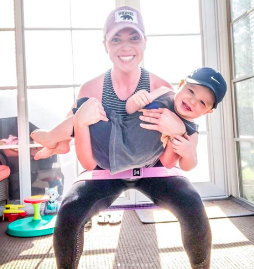 A smiling woman doing squats while holing her child in her arms
