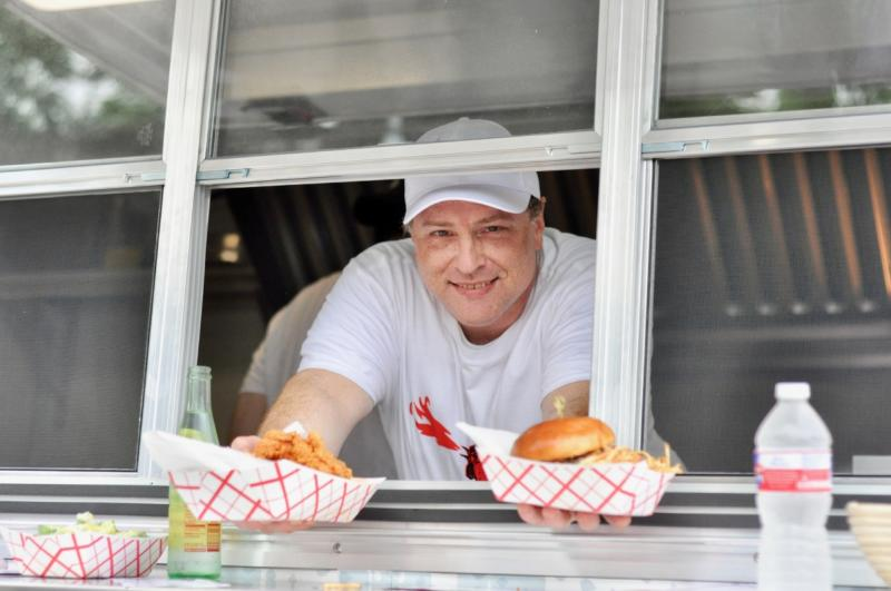 Chef serving chicken sandwich from food trailer at Tumble 22 in austin texas